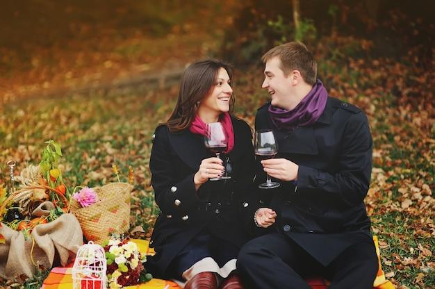 Romantisch jong stel dat een geweldige tijd heeft, met een glas wijnstok. picknick