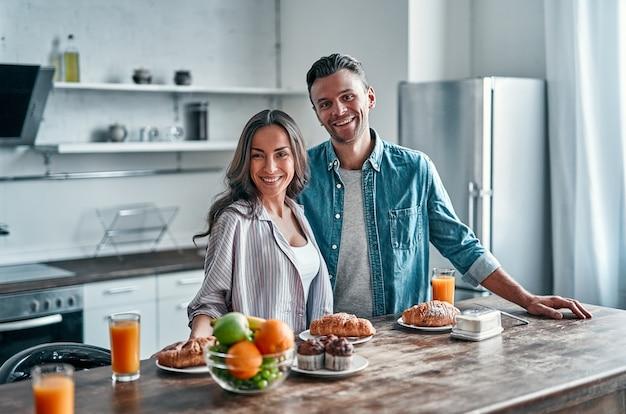 Romantisch jong stel dat in de keuken voorbereidingen treft om te ontbijten. aantrekkelijke jonge vrouw en knappe man genieten van tijd samen doorbrengen terwijl ze op de lichte, moderne keuken staan.