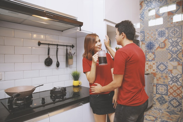 Romantisch jong stel drinken en praten in de keuken
