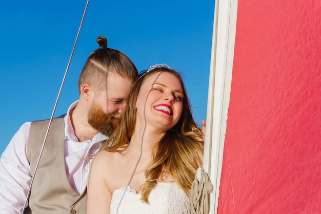 Romantisch jong stel net getrouwd staande op een zeilboot bij de mast naar een scharlaken zeil