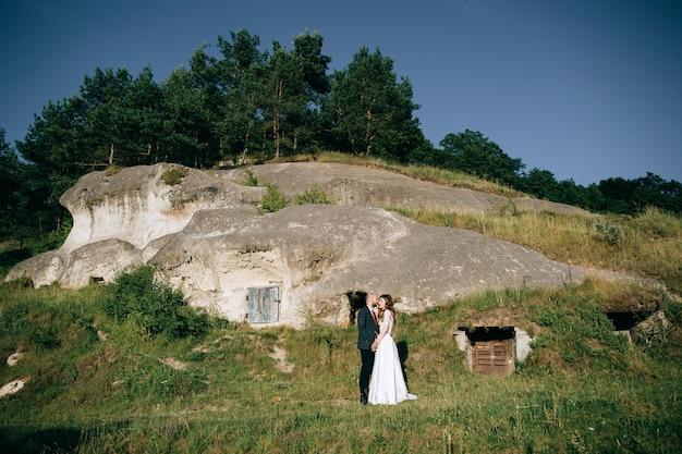 Romantisch jonggehuwde paar knuffelen in de buurt van berg