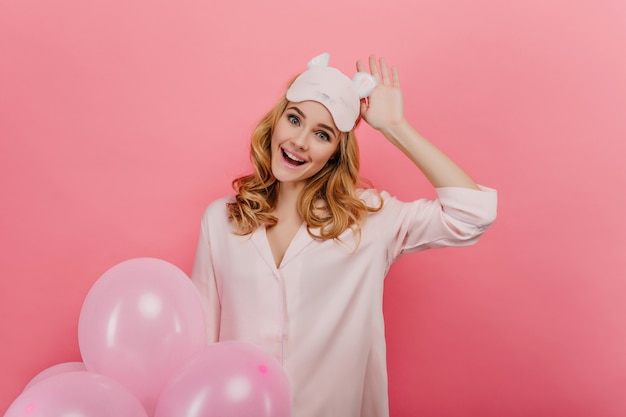 Romantisch lachen meisje haar slaapmasker aan te raken en heldere ballonnen te houden. binnenportret van prachtige krullende dame die op roze muur wordt geïsoleerd.