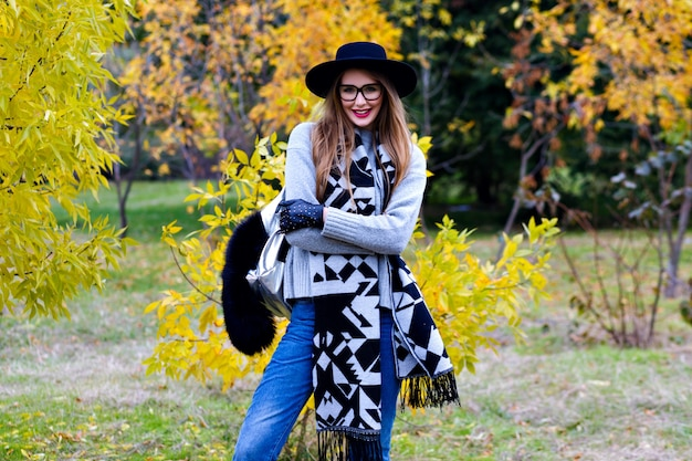 Romantisch langharige meisje poseren met de uitdrukking van het kusgezicht tijdens het wandelen in de herfstpark. openluchtportret van elegante europese jonge vrouw in jeans en hoed die zich naast gele struik bevinden.