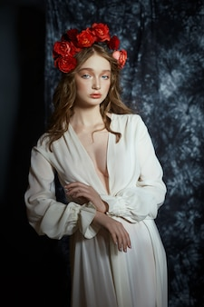 Romantisch lenteportret van een jonge blonde vrouw met een krans van roodroze bloemen, een meisje in een lichtwitte jurk. een vrouw met een perfecte huid poseert op een donkere achtergrond