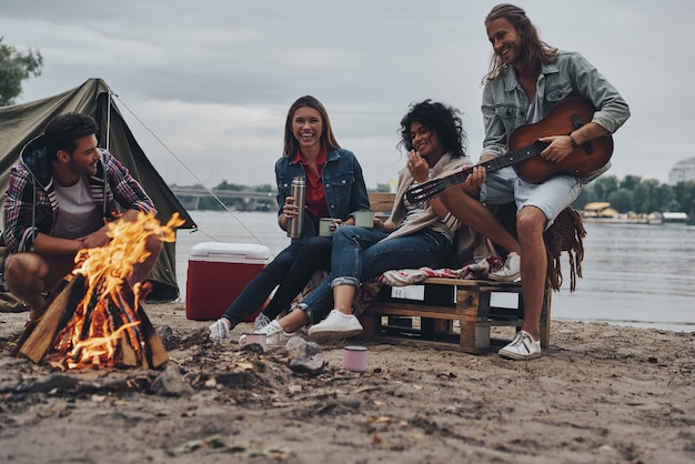 Romantisch liedje spelen. groep jongeren in vrijetijdskleding glimlachend