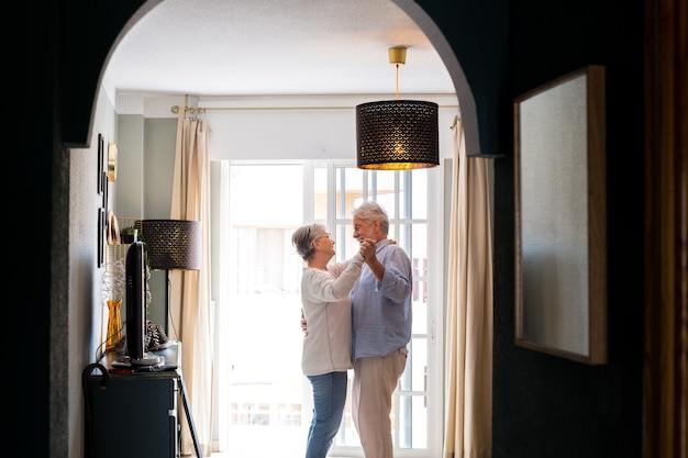 Romantisch liefdevol senior koppel hand in hand genietend van samen dansen in de woonkamer van het huis, paar omarmen terwijl ze elkaars hand vasthouden thuis