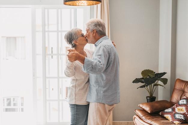 Romantisch liefdevol senior koppel hand in hand genietend van samen dansen terwijl ze elkaar kussen in de woonkamer van het huis, paar zoenen en omhelzen terwijl ze elkaars hand vasthouden thuis