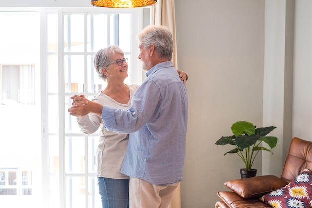 Romantisch liefdevol senior paar hand in hand genieten van samen dansen in de woonkamer van het huis, bejaarde gelukkige paar vieren door te dansen in de woonkamer.