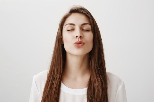 Romantisch meisje dat voor kus met gesloten ogen leunt