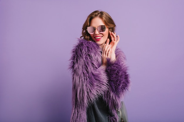 Romantisch meisje in een stijlvolle paarse outfit poseren met een verlegen glimlach in de studio