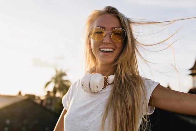 Romantisch meisje met grote koptelefoon echte positieve emoties uitdrukken in goede zomerdag.