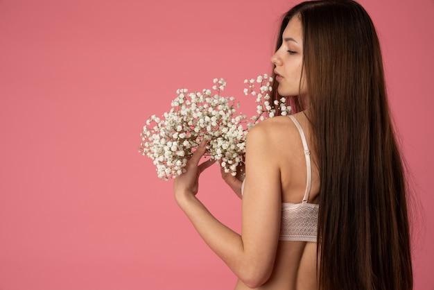 Romantisch meisje met lang donkerbruin haar gekleed in witte kanten beha die zich terug naar de camera bevindt en witte bloemen houdt