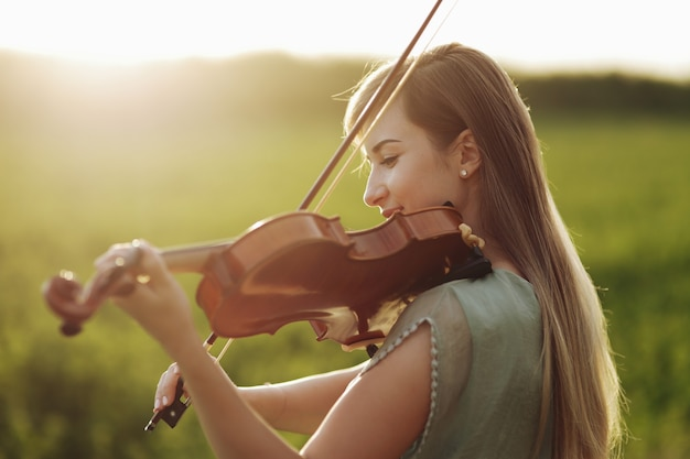 Romantisch meisje met losse haren viool spelen in zonsonderganglicht