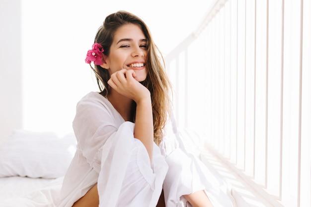 Romantisch meisje met sluwe glimlach in vintage blouse zittend op bed en haar kin met hand aan te raken. portret van dromerige schattige jonge vrouw met bloem in kapsel rusten in slaapkamer in de ochtend