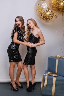 Romantisch meisje wegkijken met een glimlach, terwijl zus op haar verjaardag omhelst. indoor portret van twee opgewonden dames draagt trendy zwarte schoenen met hoge hakken en dansen tijdens het evenement.