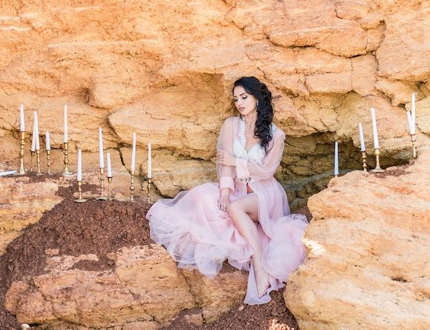 Romantisch meisjesportret van krullende vrouw met lang haar en lichte make-up. ochtend van de bruid. roze transparant