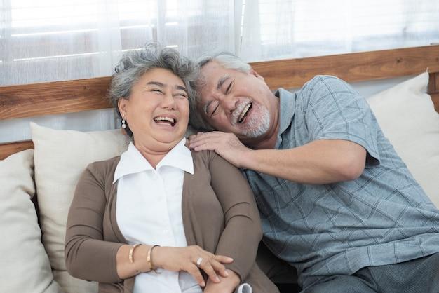 Romantisch met grote glimlach en lachen van senior oudere aziatische grootmoeder en grootvader zitten op bank in huis, pensioen oudere levensstijl