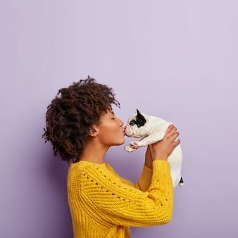Romantisch moment. curly haired donkere huid vrouwelijke hondeneigenaar geniet van kus met schattig huisdier