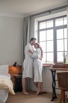 Romantisch moment. een man in een witte badjas die een vrouw omhelst bij het raam