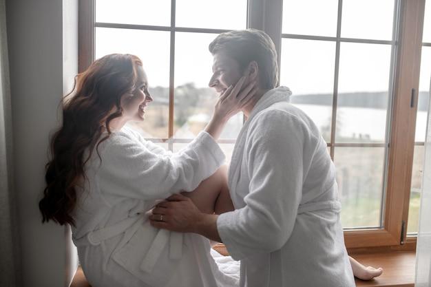 Romantisch moment. een stel in witte badjassen dat bij het raam staat en er romantisch uitziet