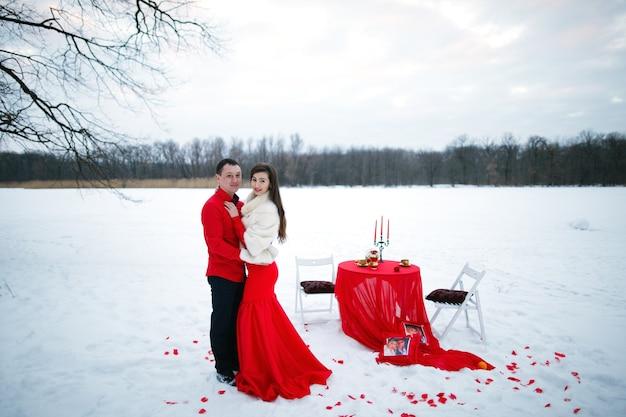 Romantisch mooi liefdesverhaal van geliefden in rode kleren poseren zittend aan een tafel op een achtergrond van sneeuw