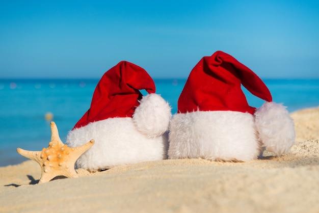 Romantisch nieuwjaar op zee. kerst vakantie. kerstmutsen op zandstrand