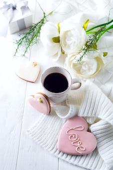 Romantisch ontbijt op bed. koffie, koekjes, geschenkdoos en bloem op houten tafel. valentijnsdag concept