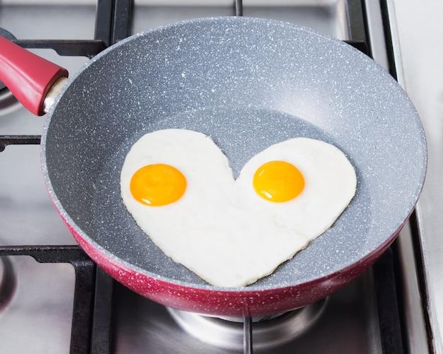 Romantisch ontbijt - roerei in de vorm van een hart op een rode koekenpan op een fornuis