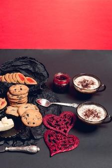 Romantisch ontbijt twee kopjes koffie, cappuccino met chocoladekoekjes en koekjes