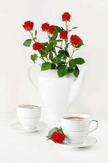 Romantisch ontbijt voor twee op een valentijnsdag met thee en een boeket rode rozen. hou van wenskaart concept