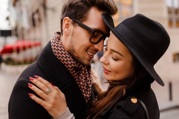 Romantisch paar aangezicht tot aangezicht knuffelen en glimlachen. warme gezellige kleuren, winterstemming. knappe man en elegante donkerharige vrouw wandelen in de stad.