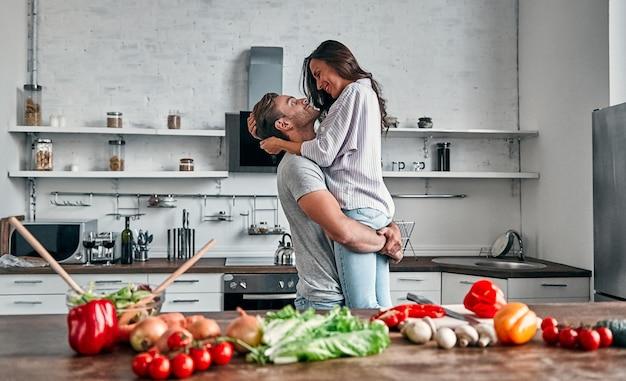 Romantisch paar dansen in de keuken. knappe man en aantrekkelijke jonge vrouw hebben samen plezier tijdens het maken van salade. gezond levensstijlconcept.