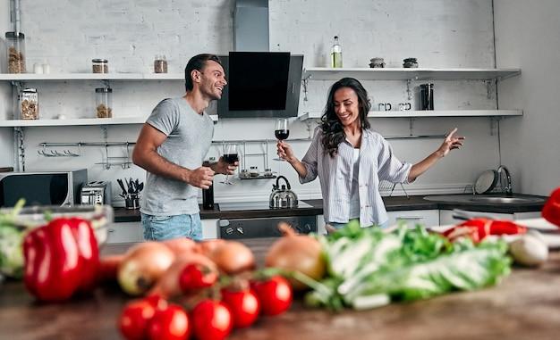 Romantisch paar dansen in de keuken met glazen wijn. knappe man en aantrekkelijke jonge vrouw hebben samen plezier tijdens het maken van salade. gezond levensstijlconcept.