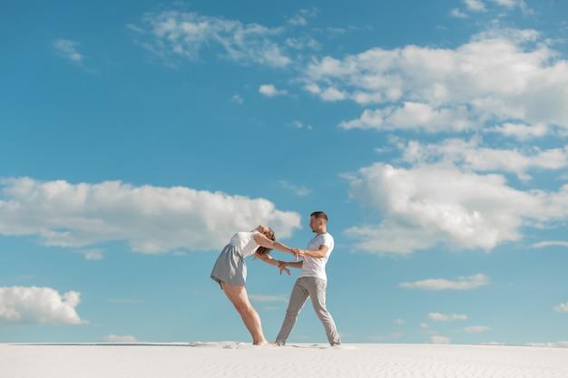 Romantisch paar dansen in zand woestijn