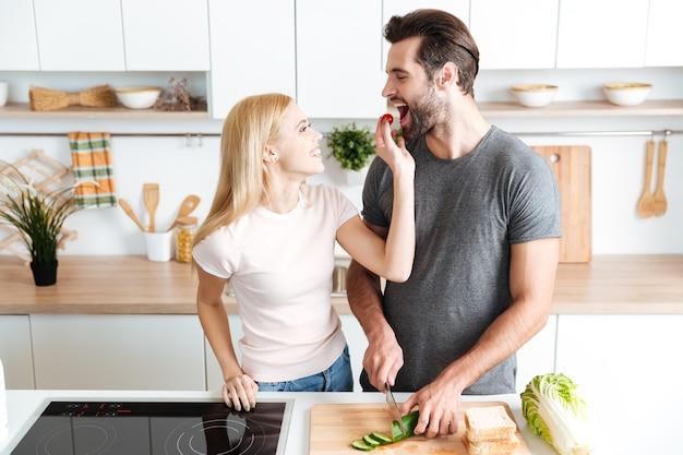Romantisch paar dat diner in de keuken thuis voorbereidt