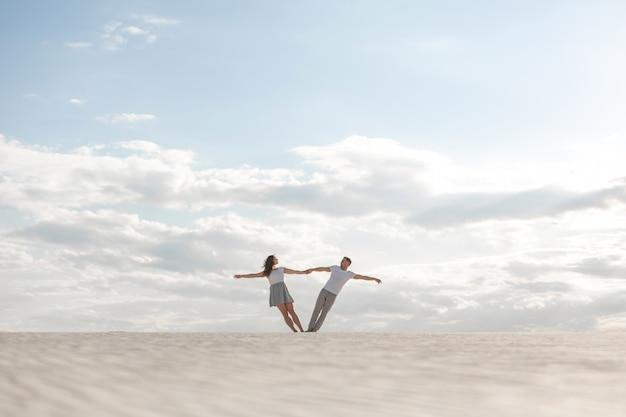 Romantisch paar dat houdend elkaar wapens in zandwoestijn danst