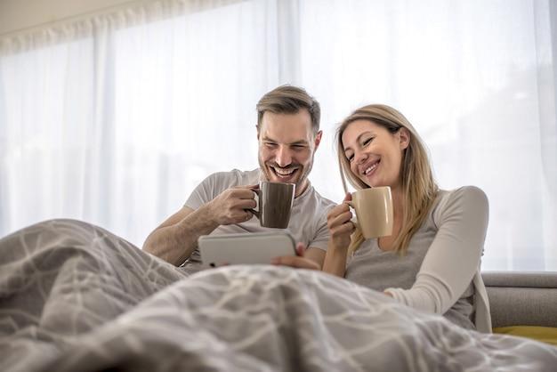 Romantisch paar dat in het bed ligt en koffie drinkt en iets op hun telefoon bekijkt