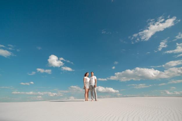Romantisch paar dat in zandwoestijn bij blauwe hemel danst