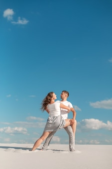 Romantisch paar dat in zandwoestijn bij blauwe hemelachtergrond danst