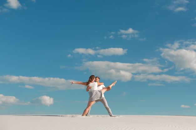 Romantisch paar dat in zandwoestijn bij blauwe hemelachtergrond danst.