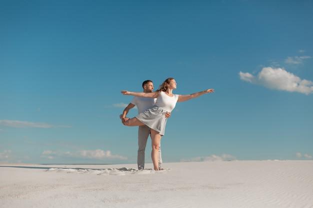 Romantisch paar dat in zandwoestijn bij blauwe hemelscène danst