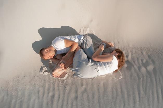 Romantisch paar dat op wit zand legt
