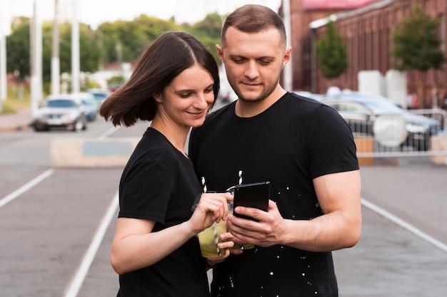 Romantisch paar dat telefoon bekijkt