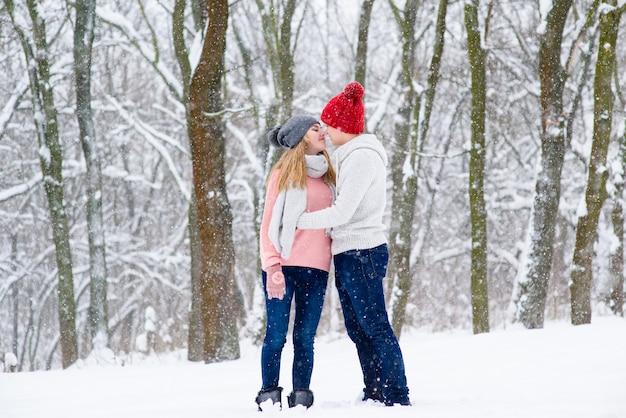 Romantisch paar in gebreide hoeden gaan kussen tijdens sneeuwval