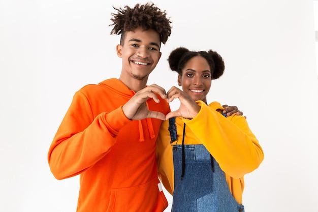 Romantisch paar in kleurrijke kleding die samen hartvorm met vingers tonen, die over witte muur wordt geïsoleerd