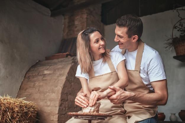 Romantisch paar in liefde die aan pottenbakkerswiel samenwerken en kleipot beeldhouwen