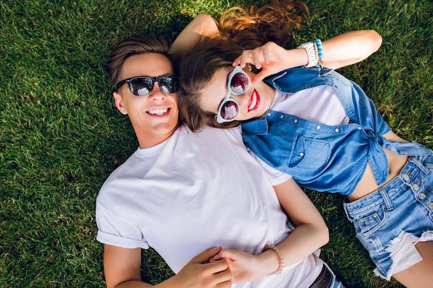 Romantisch paar jonge mensen in zonnebril ligt op gras in park. meisje met lang krullend haar ligt op de schouder van knappe jongen in wit t-shirt. uitzicht van boven.