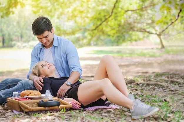 Romantisch paar met een picknick ontspannen in het park.