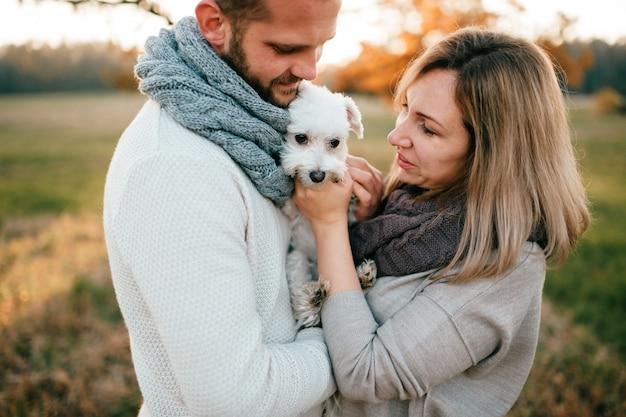 Romantisch paar met weinig puppyportret bij aard.