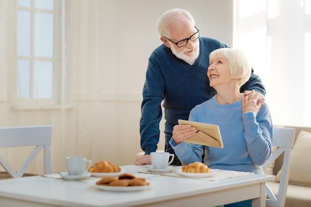 Romantisch paar. mooie rijpe vrouw die geluk voelt terwijl ze naar haar man kijkt en fotolijst vasthoudt